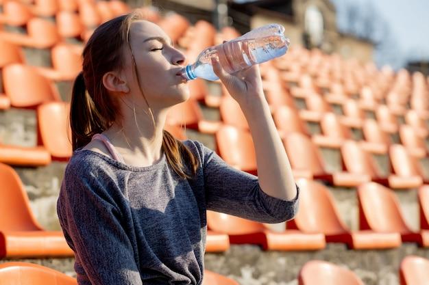 Sportliche junge frau in sportbekleidung, die sich nach hartem training entspannt, sitzt und trinkt wasser aus einer speziellen sportflasche, nachdem sie auf einem stadion gelaufen ist