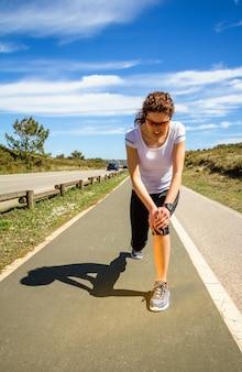 Sportliche junge frau in sportkleidung, die ihr knie durch schmerzhafte verletzungen während eines trainings im freien berührt. konzept für sportverletzungen.