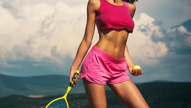 Sportliche junge frau. junge frau mit athletischem körper. glückliches aktives weibliches training. schöne attraktive fitnessfrau. starke und entschlossene frau in sportbekleidung. sport und gesunder lebensstil.