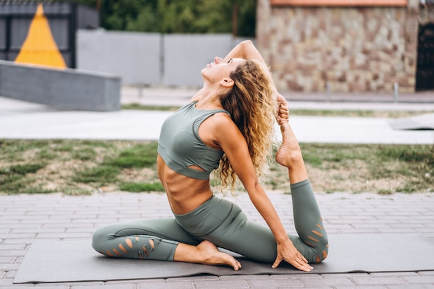 Sportliche junge frau mit dem langen haar im grauen trainingsanzug, der übungen auf der straße ausdehnend tut