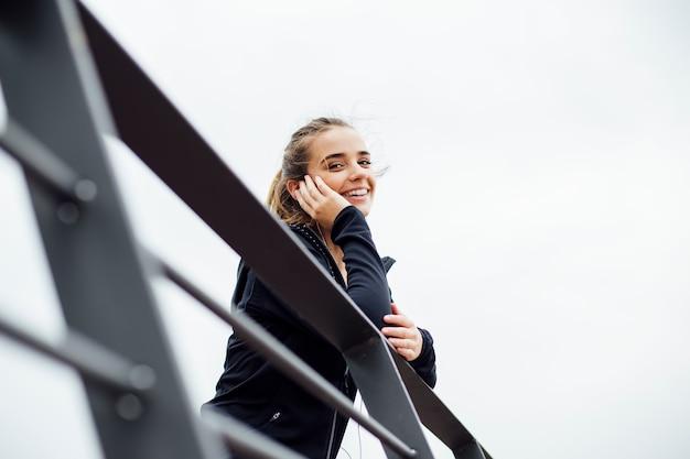 Sportliche junge frau mit den kopfhörern, die auf zaun sich lehnen und weg draußen schauen