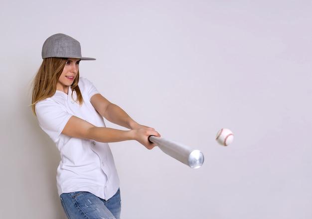 Sportliche junge frau mit einem baseballschläger schlägt den ball