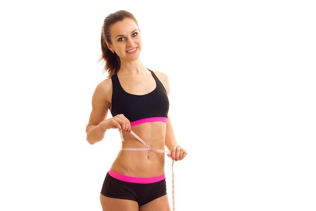 Sportliche junge frau mit elastischem taillenmaßband misst bauch auf einer weißen wand isoliert