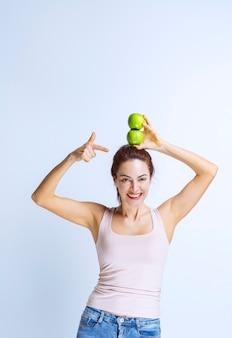 Sportliche junge frau mit grünen äpfeln über dem kopf