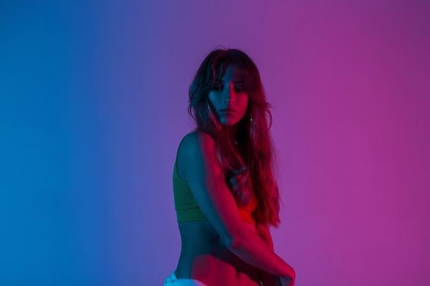 Sportliche junge frau mit langen haaren in einem modischen top posiert in einem raum auf blauem, farbenfrohem hintergrund. sexy mädchenmodemodell in trendiger kleidung steht im studio mit hellem neonrosalicht.