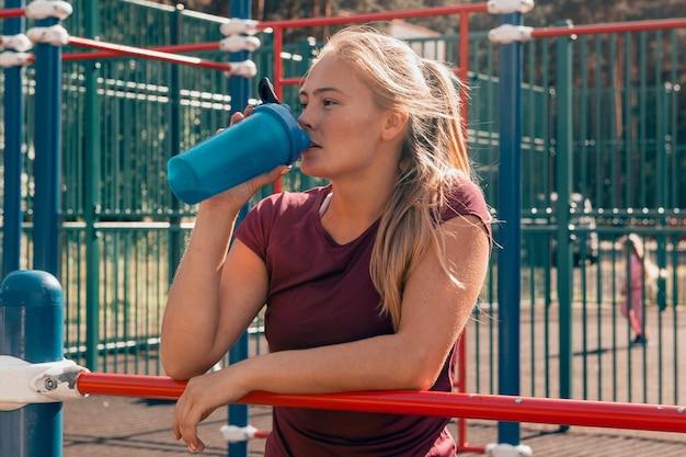 Sportliche junge frau mit wasserschüttler nach dem training auf dem sportplatz