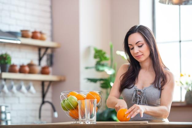 Sportliche junge frau schneidet frische orange für fruchtsaft in der küche. horizontale innenaufnahme.