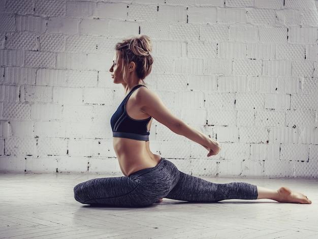 Sportliche junge frau, welche die yogapraxis lokalisiert auf weißem hintergrund tut