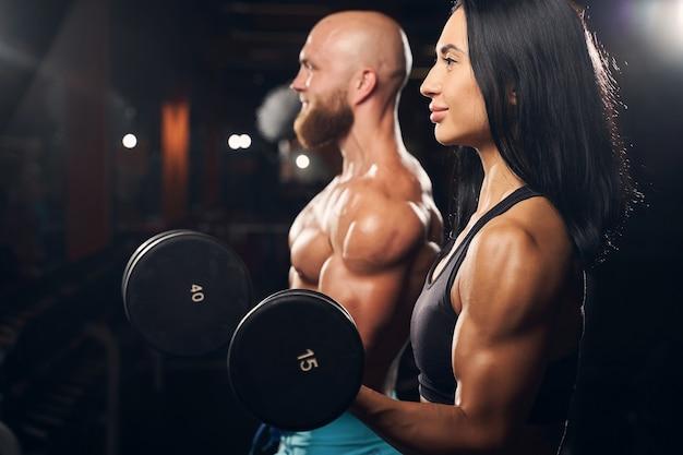 Sportliche junge leute, die energisch aussehen und hanteln heben, während sie im fitnessstudio trainieren