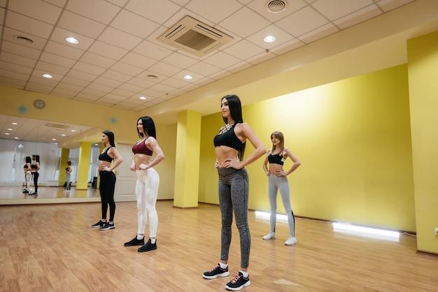 Sportliche junge mädchen beschäftigen sich in einer gruppenklasse mit fitness und aerobic. fitness, gesunder lebensstil