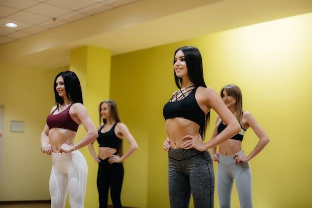 Sportliche junge mädchen beschäftigen sich in einer gruppenklasse mit fitness und aerobic. fitness, gesunder lebensstil.