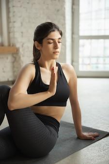 Sportliche junge muslimische frau, die online yogastunden nimmt und zu hause übt
