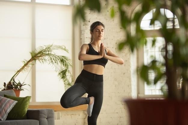 Sportliche junge muslimische frau, die zu hause yogastunden nimmt