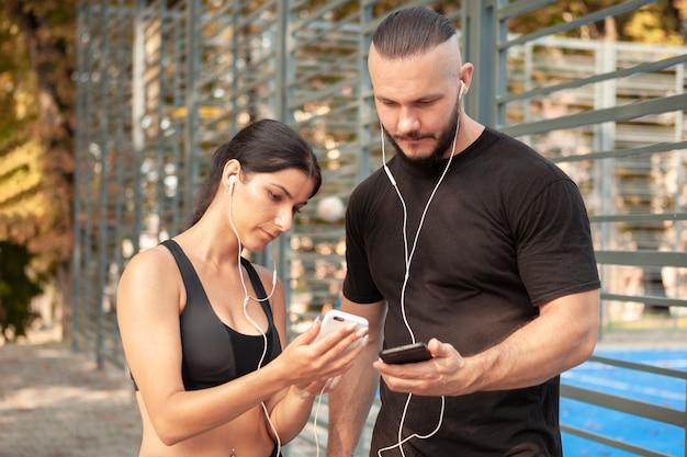 Sportliche jungen, die sich ihre telefone zeigen
