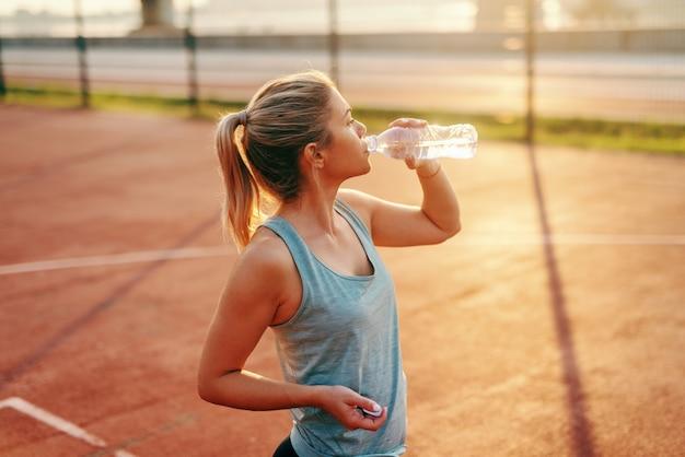 Sportliche kaukasische blonde frau, die auf dem platz steht und wasser nach morgenübungen trinkt.