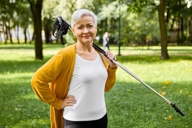 Sportliche kurzhaarige dame im ruhestand, die ja zu einem gesunden aktiven lebensstil sagt, einen stock für das nordische gehen auf ihren schultern hält, einen schönen spaziergang macht, den körper trainiert und das herz-kreislauf-system