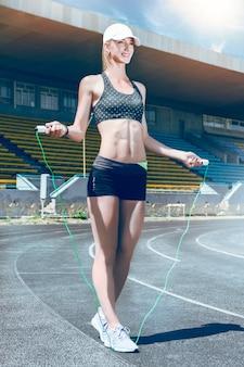 Sportliche läuferfrau der jungen eignung, die für einen lauf sich vorbereitet.