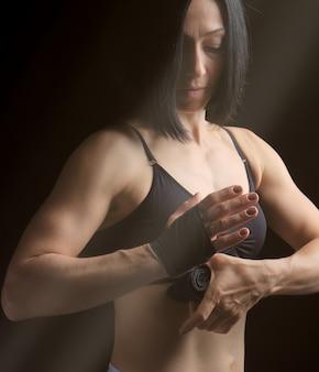 Sportliche mädchen mit schwarzen haaren spult ihre hand mit einem schwarzen elastischen verband