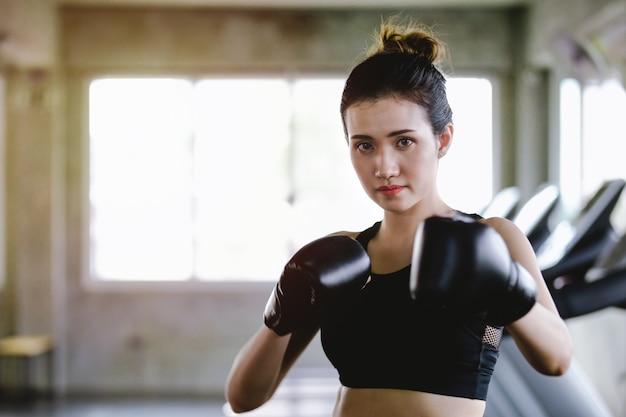 Sportliche mädchenschönheit des porträts mit den hinteren boxhandschuhen ausbildend an der turnhalle