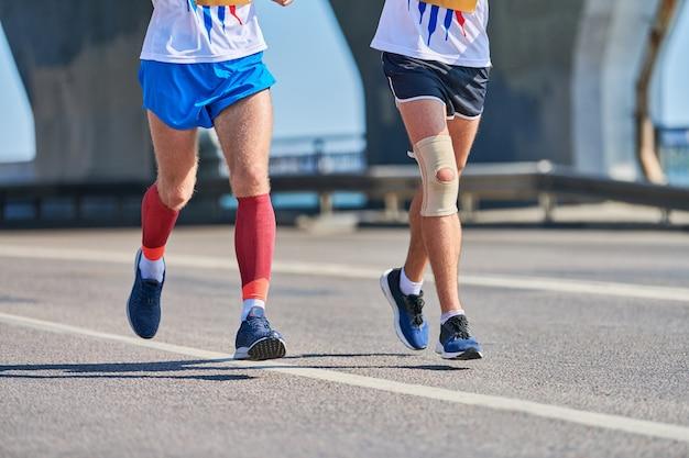 Sportliche männer, die in sportbekleidung auf stadtstraße joggen