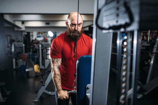 Sportliche männliche person in sportbekleidung, training auf übungsmaschine im fitnessstudio. bärtiger mann auf training im sportverein, gesunder lebensstil