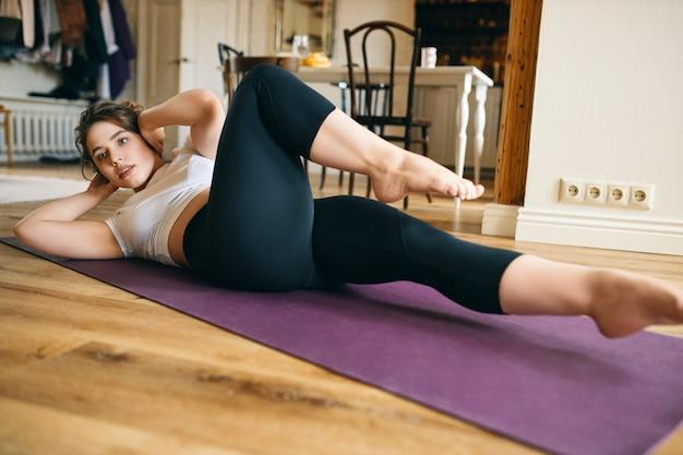 Sportliche muskulöse junge frau, die mit den händen hinter dem kopf auf dem rücken liegt, die seiten wechselt, während sie fahrrad knirscht, den ellbogen zum knie bringt, bauchmuskeln und kernmuskeln trainiert.