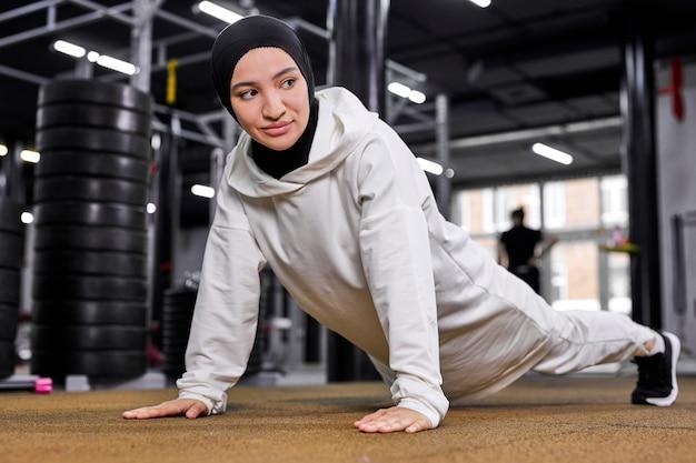 Sportliche muslimische frau, die liegestütze tut, fitnessfrau, die plankenübung ausarbeitet. die motivierte frau im hijab trainiert gerne auf dem boden im fitnessstudio
