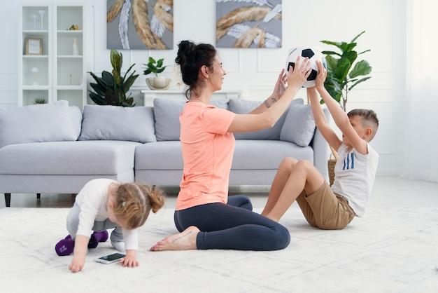 Sportliche mutter mit sohn beim morgendlichen training zu hause. mutter und sohn machen übungen zusammen, gesundes familienlebensstilkonzept