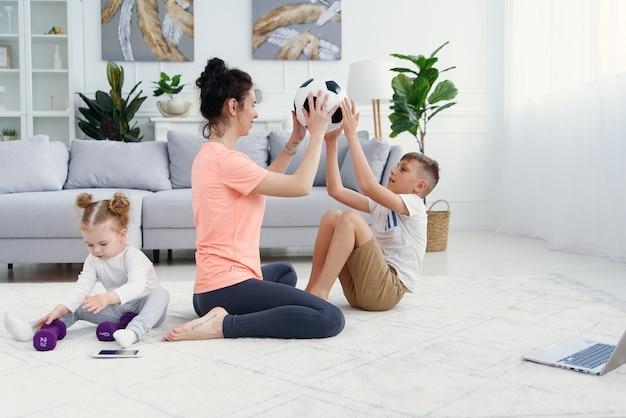 Sportliche mutter mit sohn, die morgendliches training zu hause macht, während baby spielt