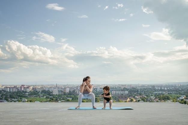 Sportliche mutter trainiert mit kleinem sohn. sportkonzept.