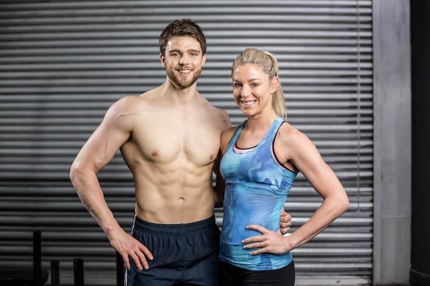 Sportliche paar posiert im fitnessstudio