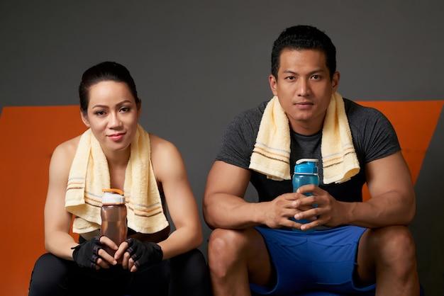 Sportliche paare, welche die kamera gesetzt auf der couch nach der trainingseinheit betrachten