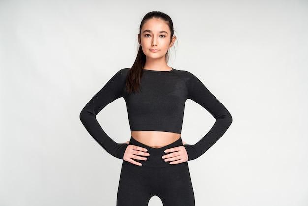 Sportliche schlanke junge frau in schwarzem top und hose gekleidet, die vor weißem wandhintergrund posiert. asiatisches mädchen, das ihre hände an ihrer taille hält und in die kamera schaut
