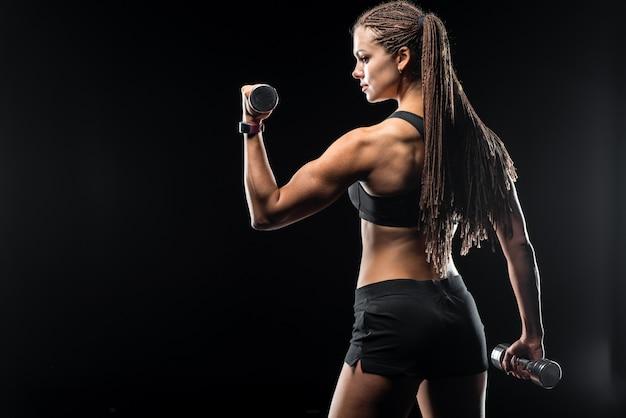 Sportliche schönheit, welche die eignung trainiert mit dummköpfen auf schwarzem hintergrund tut