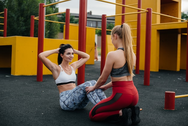 Sportliche, sexy girls machen bauchmuskelübungen im freien. fitness, gesunder lebensstil