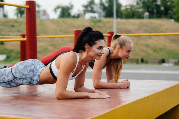 Sportliche, sexy girls stehen in der bar im freien. fitness, gesunder lebensstil