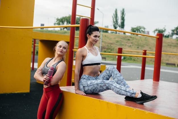 Sportliche, sexy mädchen treiben sport unter freiem himmel. fitness, gesunder lebensstil