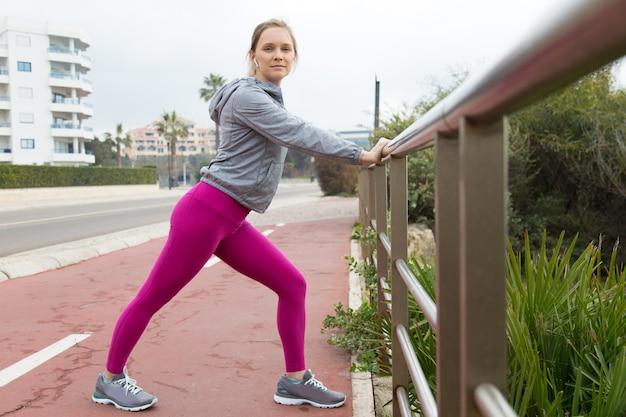 Sportliche sitzdame in den rosa gamaschen, die übung mit geländer tun