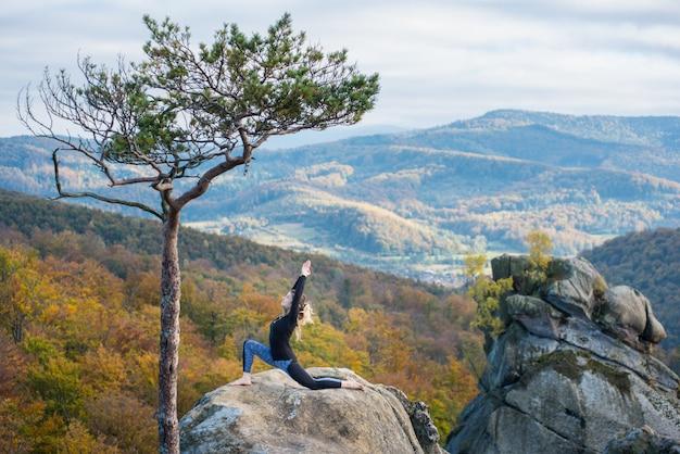 Sportliche sitzfrau übt yoga auf die oberseite des berges