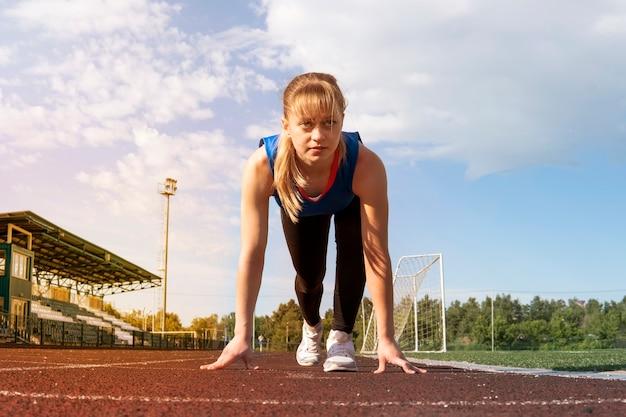 Sportliche teenager-mädchen in startposition auf dem richtigen weg. konzept der vorwärtsbewegung.