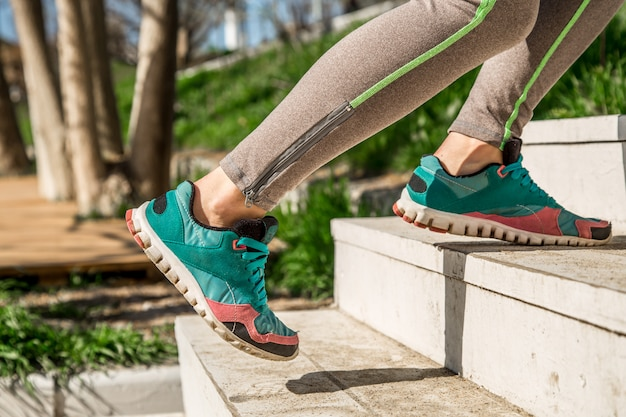 Sportliche weibliche beine steigen die treppe hinauf