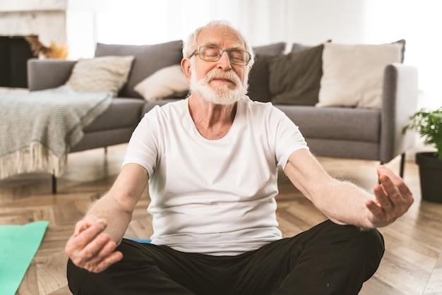 Sportlicher älterer mann, der zu hause fitness- und entspannungsübungen macht - ältere menschen trainieren, um gesund und fit zu bleiben