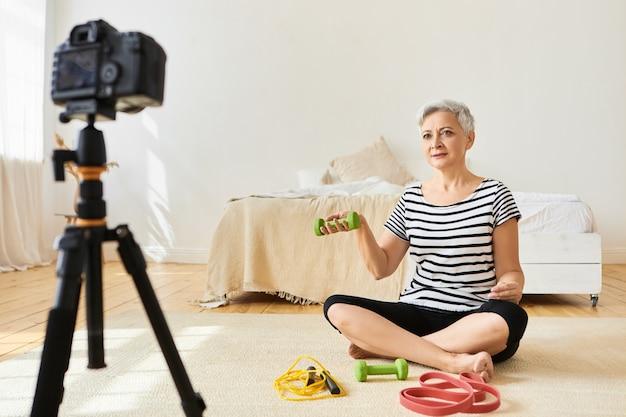 Sportlicher älterer weiblicher fitnesstrainer mit kurzen grauen haaren, die auf boden mit grünen hanteln trainieren, video-tutorial über kamera auf stativ aufzeichnend. menschen, alter und gesunder aktiver lebensstil