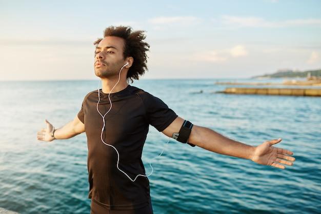 Sportlicher afroamerikanischer mann, der seine arme vor dem training im freien streckt. schlanker und starker männlicher athlet, der ein schwarzes t-shirt trägt, die arme offen hält und frische seeluft atmet.