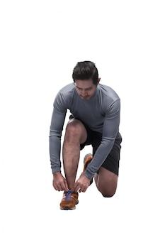Sportlicher asiatischer mann setzen sich, die spitzee binden, die zum laufen bereit sind