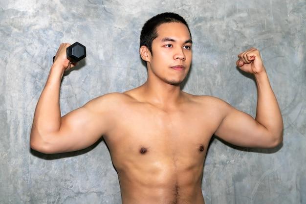 Sportlicher asiatischer manntrainingsarm des perfekten starken bodybuilders mit dummkopf auf hintergrund.