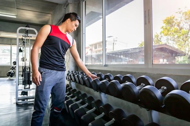Sportlicher asiatischer manntrainingsarm des perfekten starken bodybuilders mit dummkopf auf turnhalle.