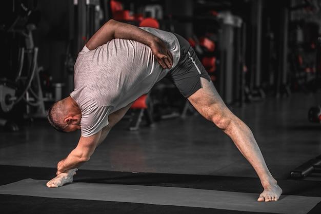Sportlicher bärtiger junger mann, der yoga praktiziert