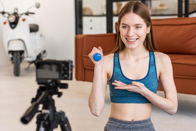 Sportlicher blogger, der hantel an der kamera zeigt