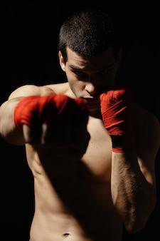Sportlicher boxer, der mit entschlossenheit und vorsicht schlägt